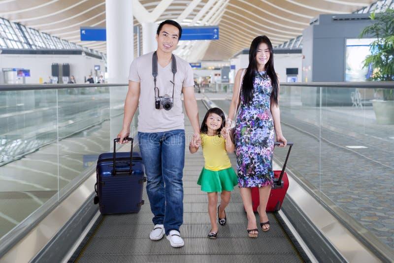 走在机场自动扶梯的年轻家庭 库存图片