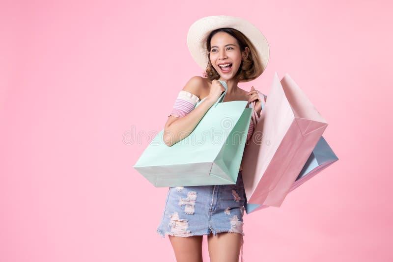 走在桃红色淡色背景的亚裔俏丽的年轻女人 微笑和拿着购物带来的她 她nice-looking可爱 免版税库存照片