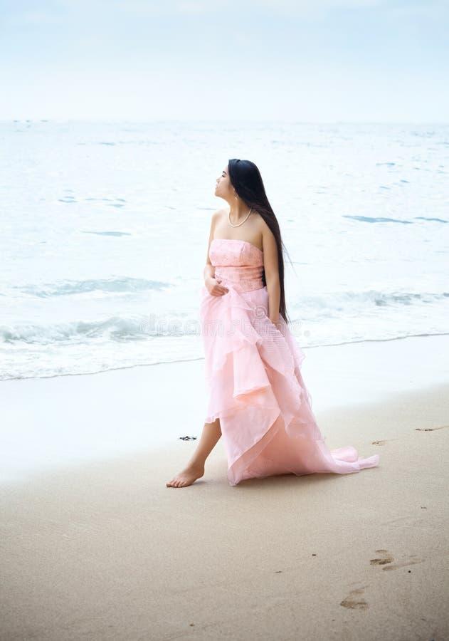 走在桃红色褂子的夏威夷海滩的美丽的年轻女人 库存图片