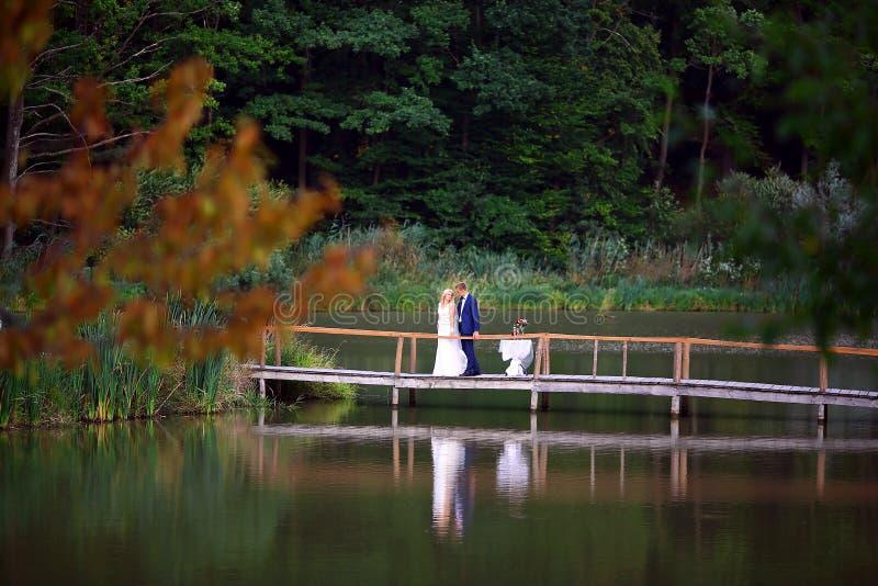走在桥梁的婚礼夫妇在日落的湖附近婚礼之日 新娘和新郎在爱,选择聚焦 免版税库存图片