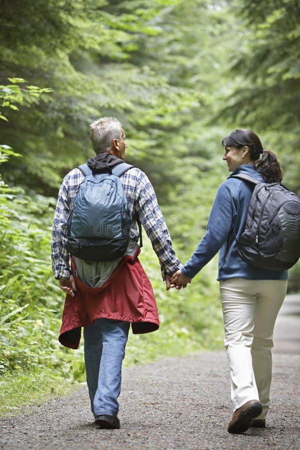走在森林公路的夫妇 免版税库存图片