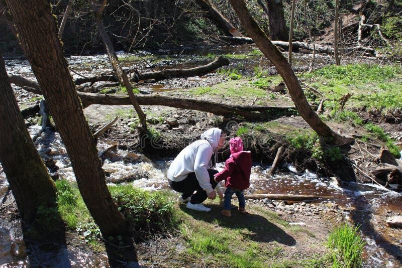 走在森林河附近的父亲和女儿 免版税图库摄影