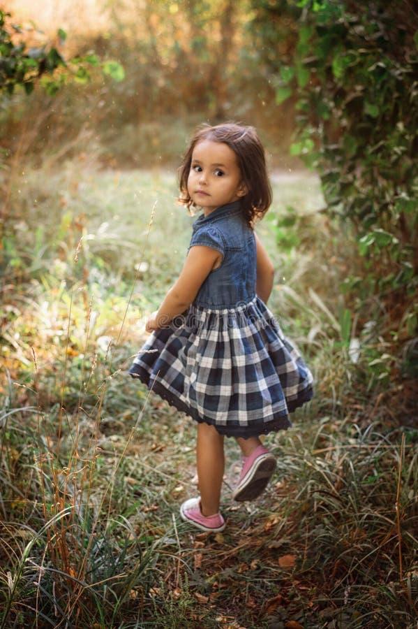 走在森林里的小甜女孩 免版税库存图片