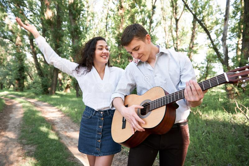 走在森林里的年轻夫妇,弹吉他和跳舞、夏天自然、明亮的阳光、阴影和绿色叶子,浪漫 库存照片