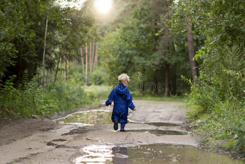 走在森林里的男婴2年通过水坑哄骗赛跑 免版税库存图片