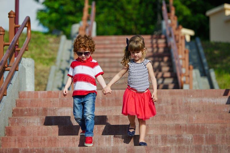 走在楼梯的男孩和女孩 免版税库存图片