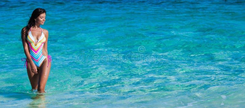 走在水中的美丽的比基尼泳装妇女 库存图片