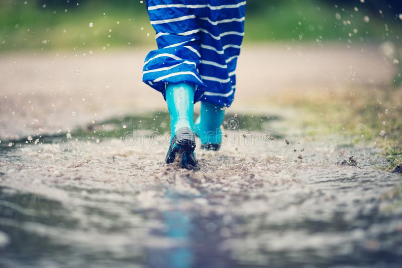 走在水坑的wellies的孩子在多雨天气 免版税图库摄影