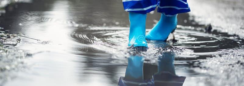 走在水坑的wellies的孩子在多雨天气 免版税库存照片