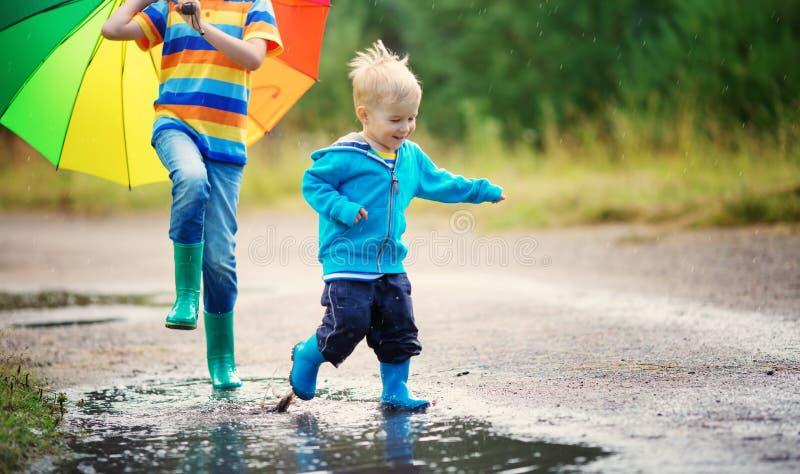 走在水坑的wellies的孩子在多雨天气 免版税库存图片