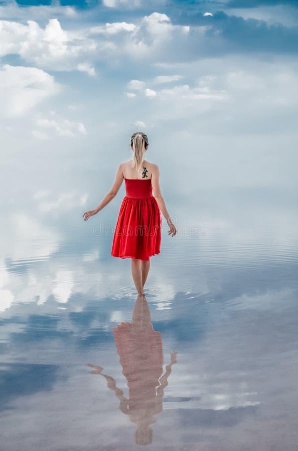 走在水的少妇穿红色礼服 天空在湖被反射 免版税库存图片