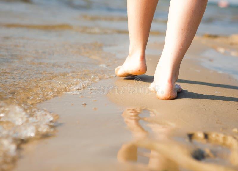 走在沙子海滩的妇女把脚印留在沙子 使旅行靠岸 免版税库存照片