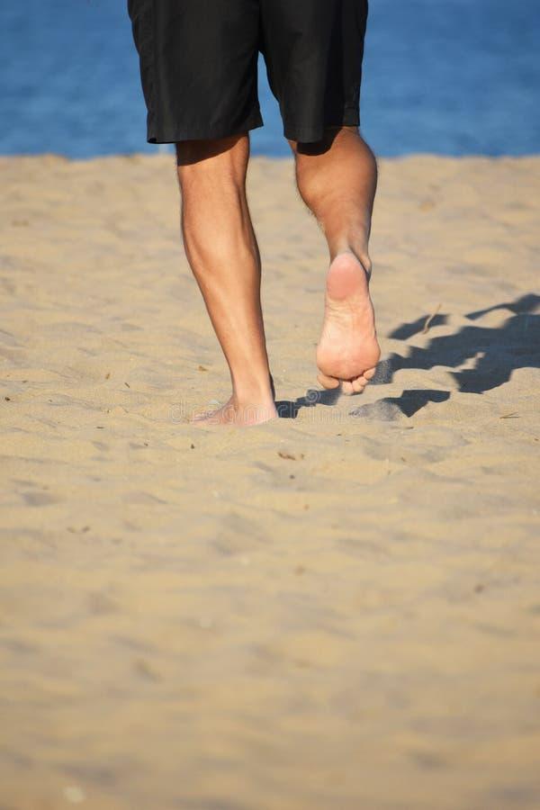 走在沙子的人由湖 库存照片