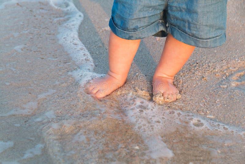 走在沙滩的赤脚靠近海 去蓝色牛仔裤的短裤的小婴孩接触海在日落 通知 免版税图库摄影