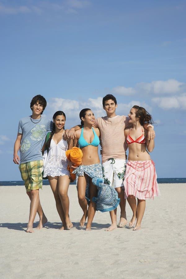 走在沙滩的愉快的少年 免版税库存图片