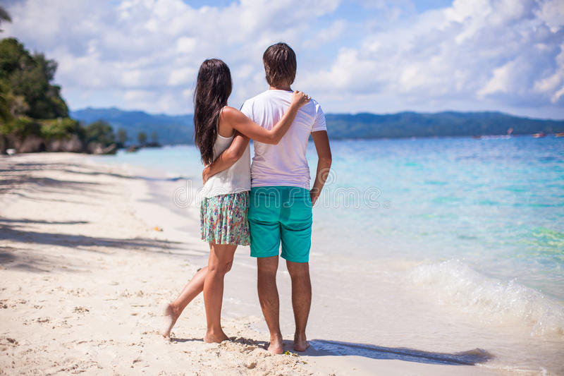 走在沙滩的年轻夫妇在海附近 库存照片