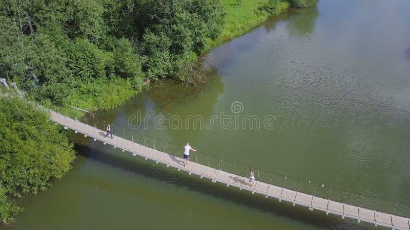 走在河的垂悬的长的金属桥梁的Unidenfied人 夹子 在桥梁的家庭在河 免版税图库摄影
