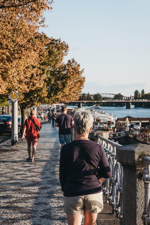 走在沿着伏尔塔瓦河河的人行道的人们在布拉格 cesky捷克krumlov中世纪老共和国城镇视图 库存照片