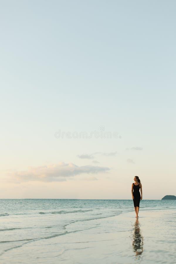 走在海洋海滩的可爱的妇女 免版税库存照片