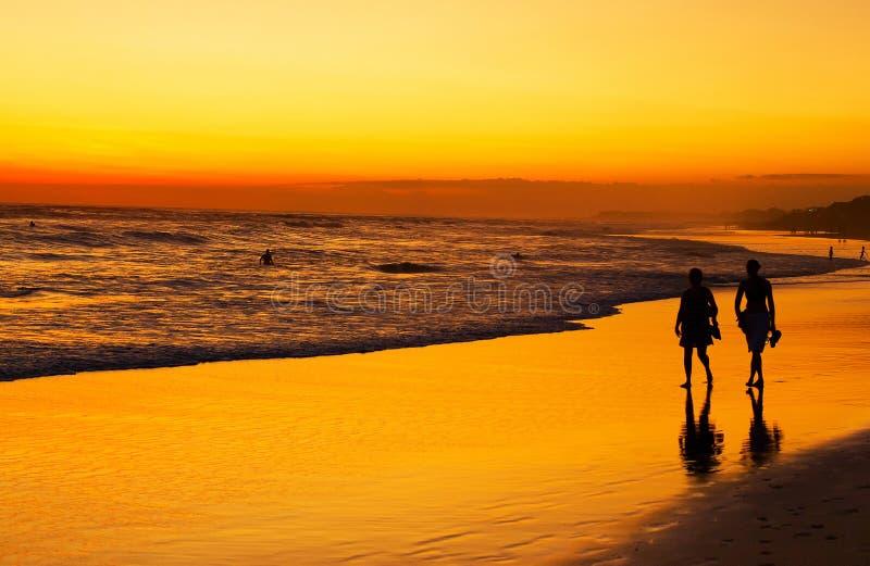 走在海洋的人们靠岸在日落 可视巴厘岛美丽的印度尼西亚海岛kuta人连续形状日落的城镇 库存照片