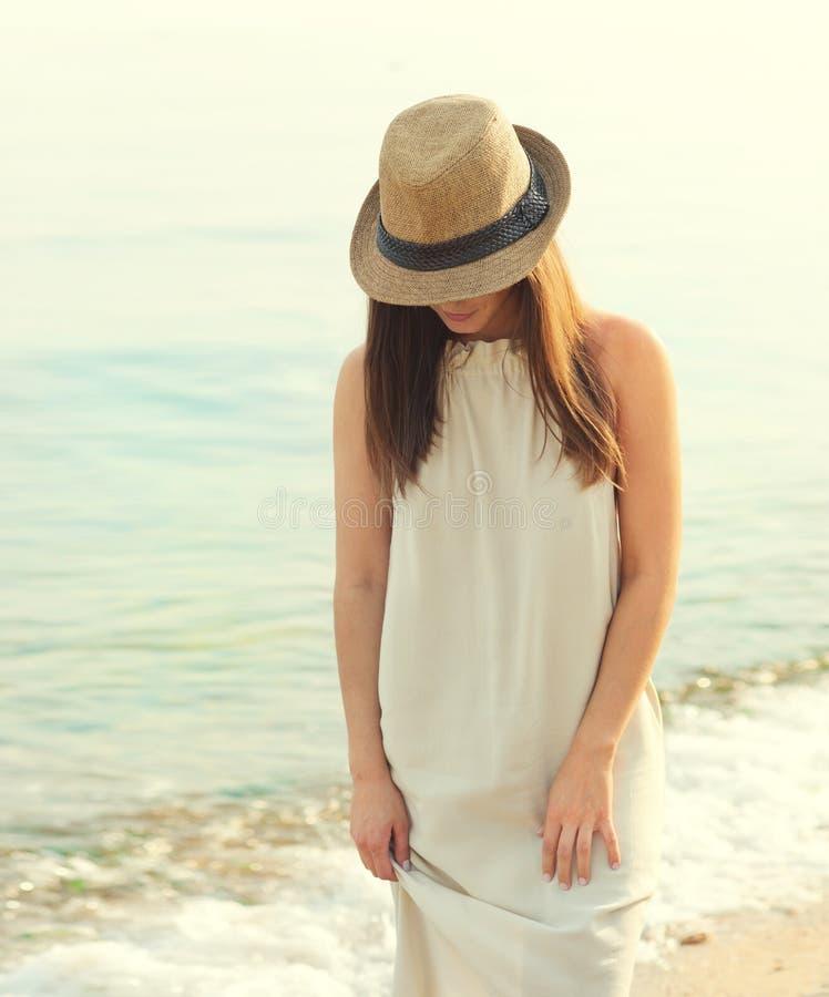 走在海海滩的愉快的微笑的妇女穿戴在白色礼服和帽子覆盖物面孔,放松和享用新鲜空气 免版税库存图片