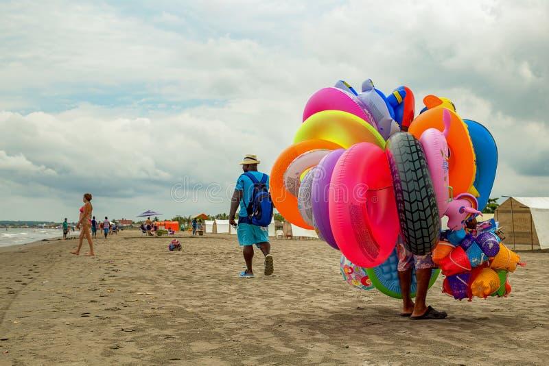 走在海滩的一位五颜六色的流动工推销员 免版税图库摄影