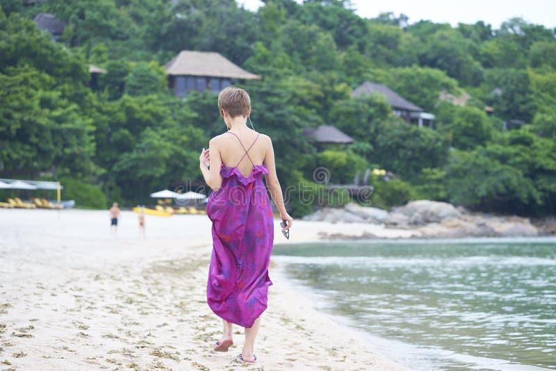 走在海滩的亚洲秀丽背面图在她的在热带手段的假期时 库存照片
