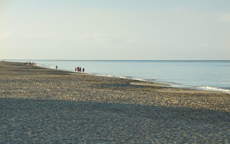 走在海滩的人们在日出,美丽的多云天空在海滩反射了 免版税图库摄影