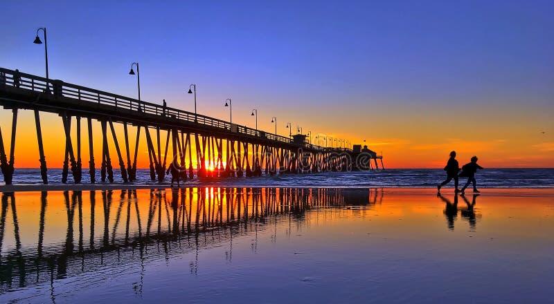 走在海滩的人的剪影和反射 库存照片