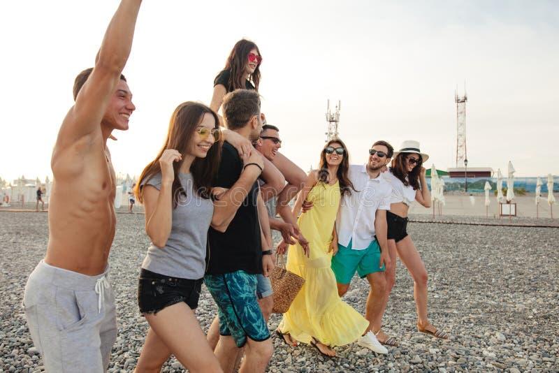 走在海滩的小组朋友,获得乐趣,妇女扛在肩上供以人员,滑稽的假期 库存照片