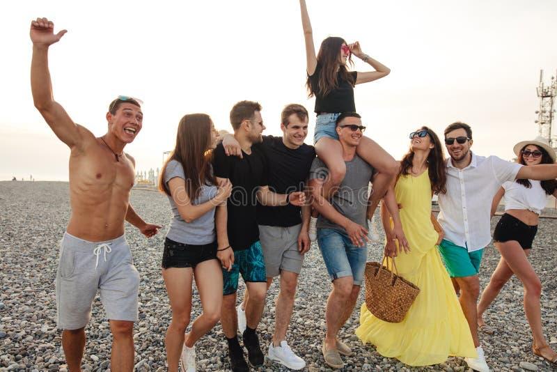 走在海滩的小组朋友,获得乐趣,妇女扛在肩上供以人员,滑稽的假期 免版税库存照片