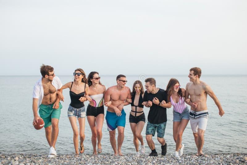走在海滩的小组朋友,获得乐趣,妇女扛在肩上供以人员,滑稽的假期 图库摄影