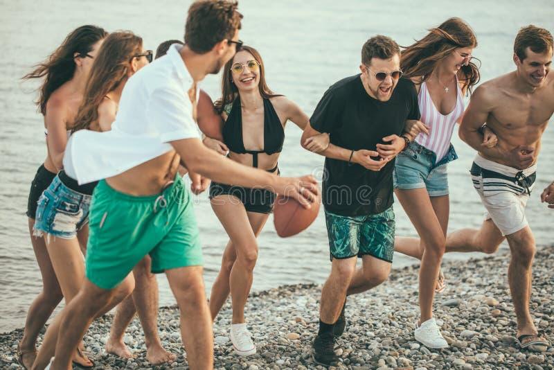 走在海滩的小组朋友,获得乐趣,妇女扛在肩上供以人员,滑稽的假期 免版税图库摄影