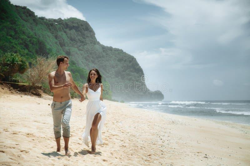 走在海滩的愉快的夫妇,旅行在巴厘岛 免版税库存照片