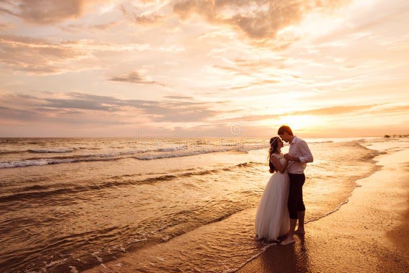 走在海滩的新婚佳偶、新娘和新郎一对美好的夫妇  华美的日落和天空 婚礼礼服, a 免版税库存照片