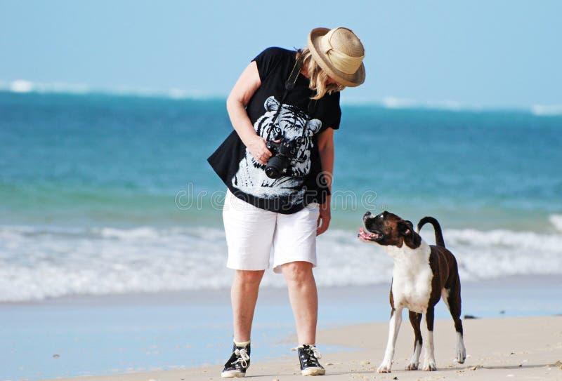 走在海滩的最佳的朋友妇女&爱犬 免版税库存图片