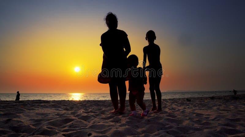 走在海滩的母亲和孩子剪影  库存照片
