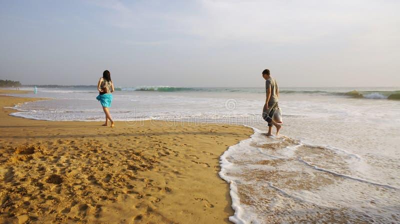 走在海滩的男孩和女孩。 库存照片