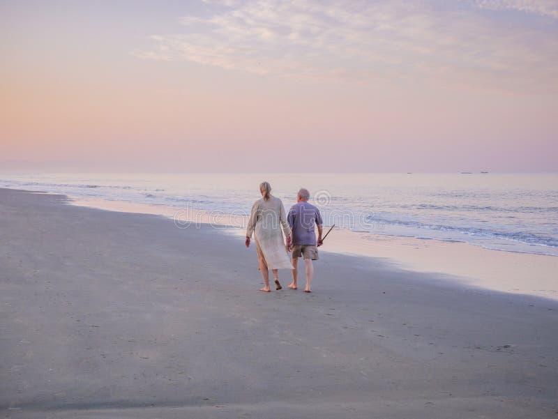走在海滩的资深夫妇 免版税库存图片