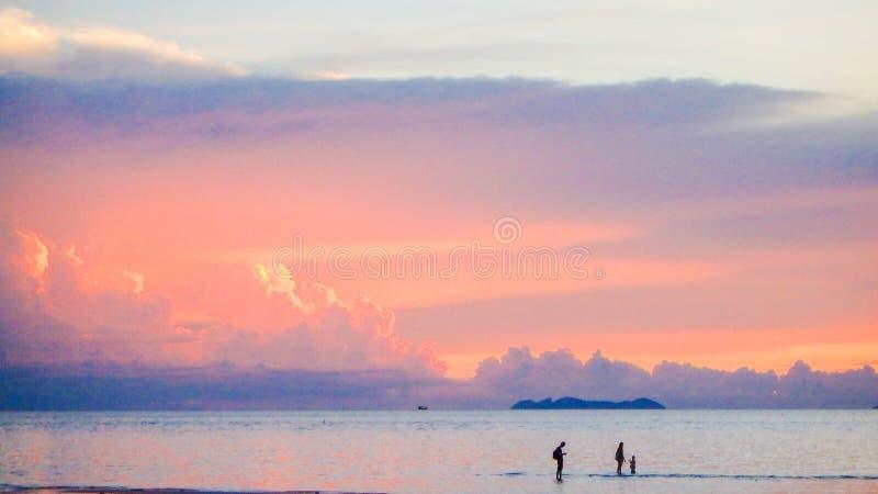走在海滩美好的淡色日落的逗人喜爱的可爱的家庭 免版税图库摄影