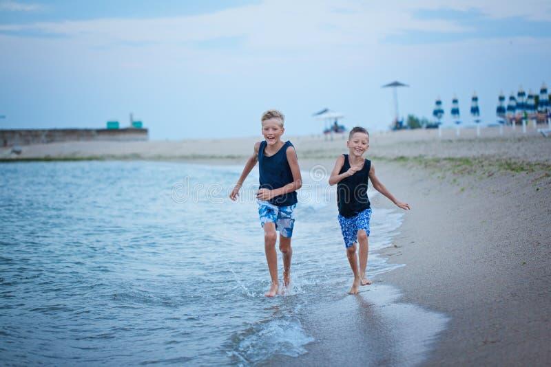 走在海的两个孩子男孩使夏天,愉快最好的朋友使用靠岸 库存图片