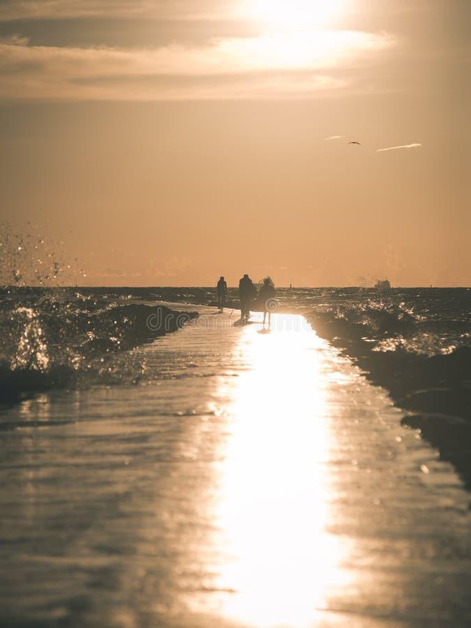 走在海葡萄酒作用的wavebreaker的人们 免版税图库摄影