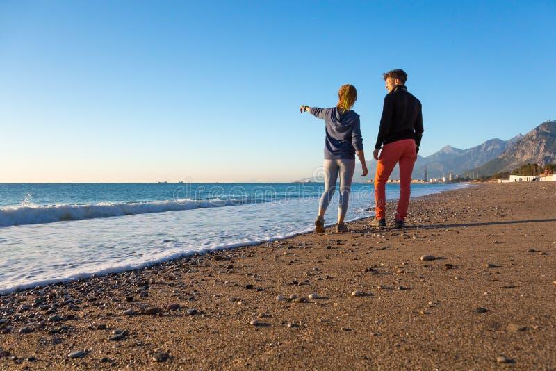 走在海滩和享受海视图的男人和妇女 库存图片