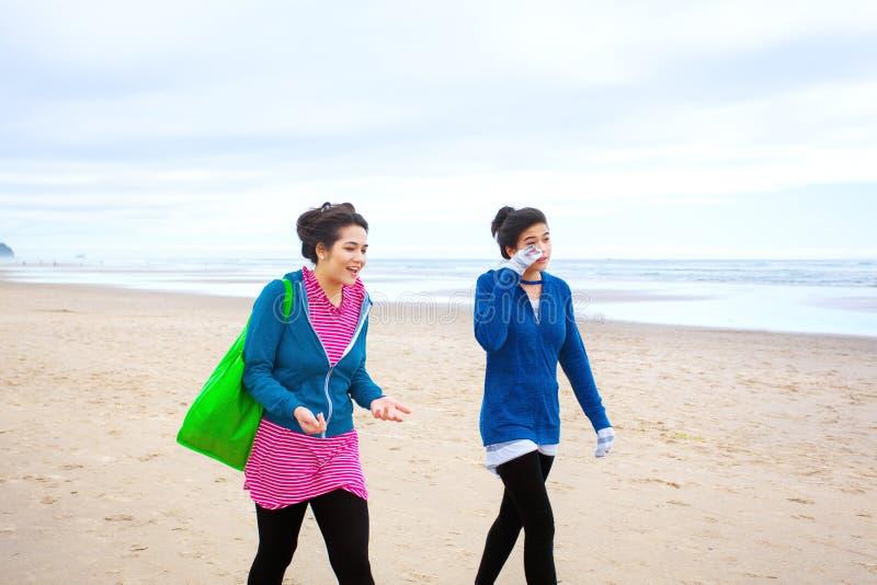 走在海滩的两个少年女孩在凉快的多云天 免版税图库摄影