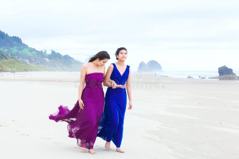 走在海滩的两个少年女孩在凉快的多云天 免版税库存图片