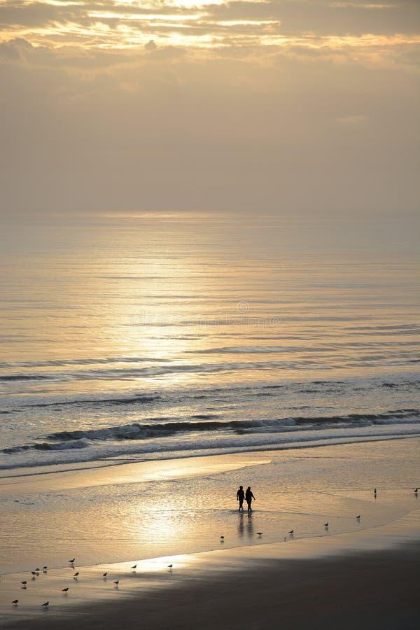 走在海滩的夫妇在日出 免版税库存照片