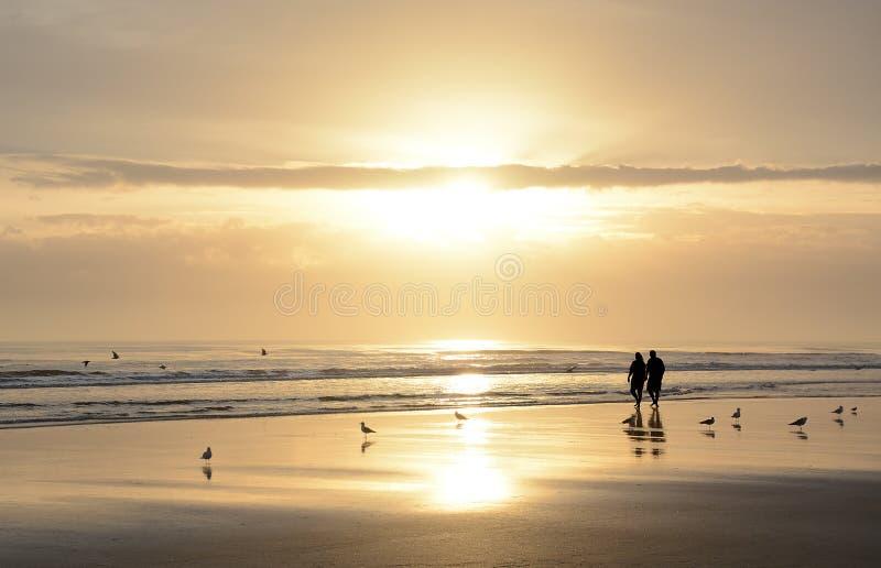 走在海滩的夫妇在日出 免版税库存图片