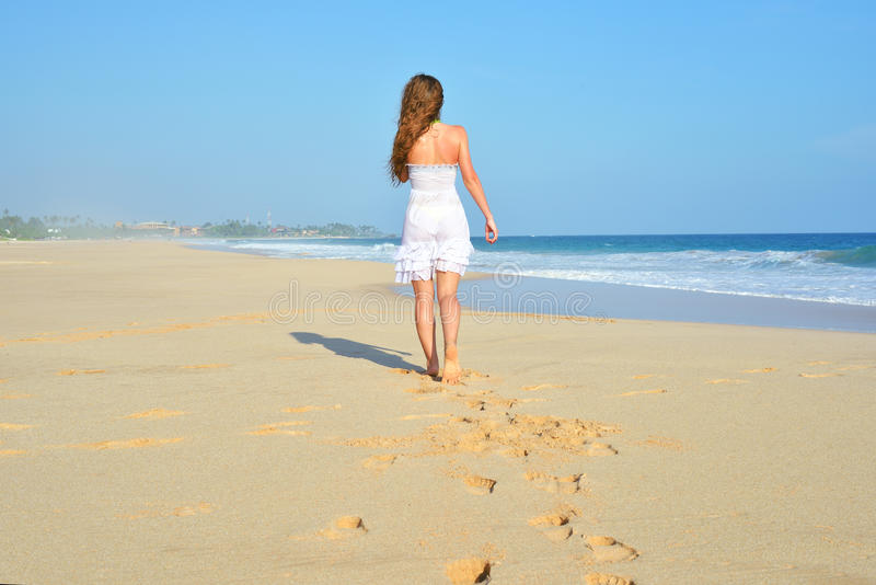 走在海滩的愉快的无忧无虑的妇女庆祝她的自由 夏天海洋和沙子的妇女背景 后面观点的女孩 库存图片