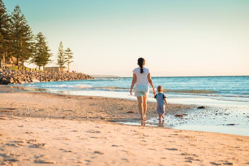 走在海滩的母亲和儿子 免版税图库摄影