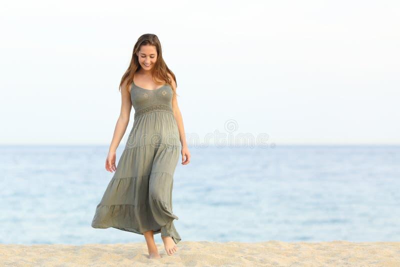 走在海滩的沙子的坦率的梦想家女孩 免版税库存图片